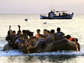 Migrants onboard an overcrowded dinghy arrive at a beach on the Greek island of Kos
