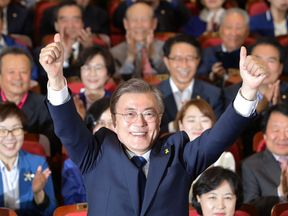 Moon Jae-in celebrates with supporters after hearing the exit poll results