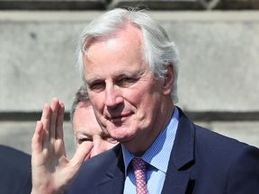 Michel Barnier waves to the media as he arrives at Leinster House in Dublin