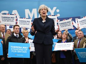 Theresa May addresses supporters in front of the Conservative party's campaign bus