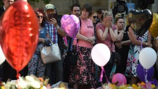 People gather ahead of a minute's silence in St Ann's Square in Manchester