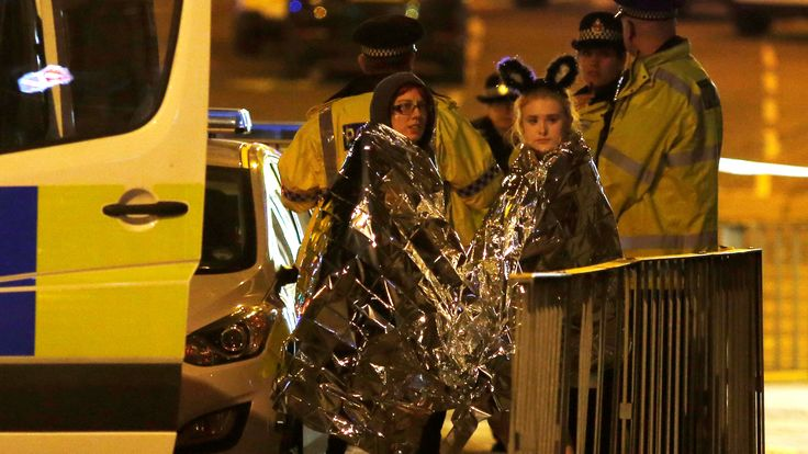 Two concert goers are wrapped in thermal blankets after the concert