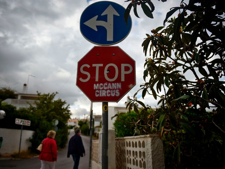 People pass by a stop sign that was vandalised with the message 'STOP McCann Circus' in Praia da Luz in Algarve, southern Portugal, on April 28, 2017
