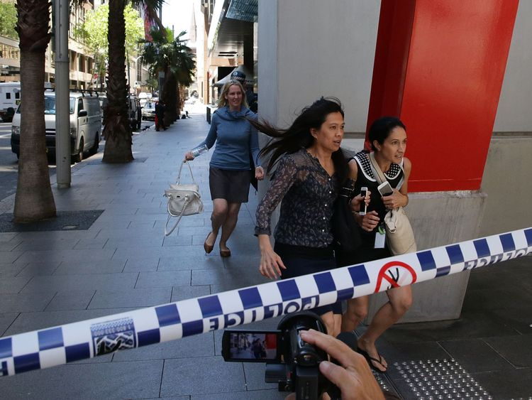 Ladies rush through Philip St past armed police at Lindt Cafe, Martin Place on December 15, 2014