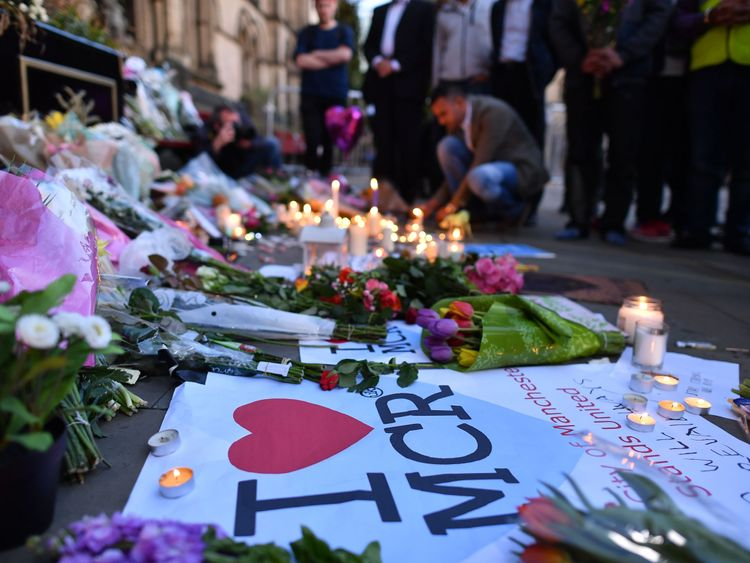 People pause in front of candles and messages set up in front of floral tributes in Albert Square in Manchester in solidarity with those killed and injured