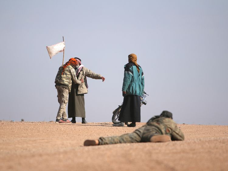 SDF fighters check people who have fled from areas where clashes are taking place north of Raqqa