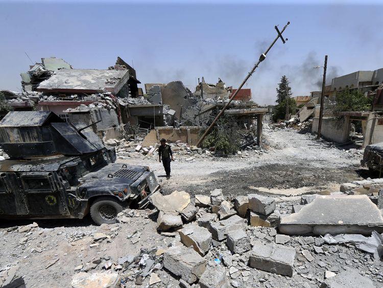 An Iraqi serviceman patrols west Mosul's al-Saha neighbourhood