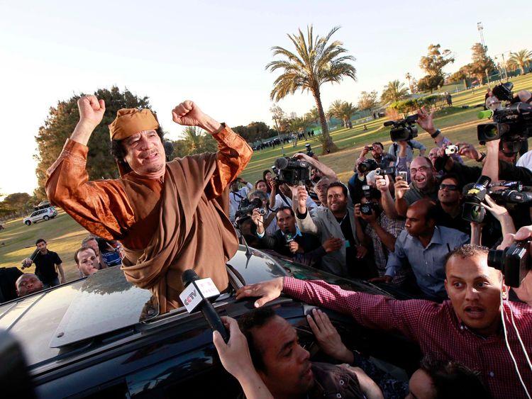 Muammar Gaddafi waves from a car in the compound of Bab Al Azizia in Tripoli