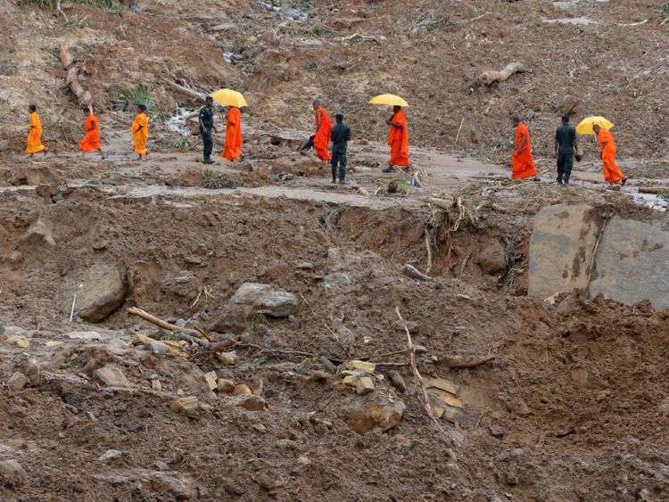 Buddhist monks cross a landslide as rescue workers search for survivors in Athweltota