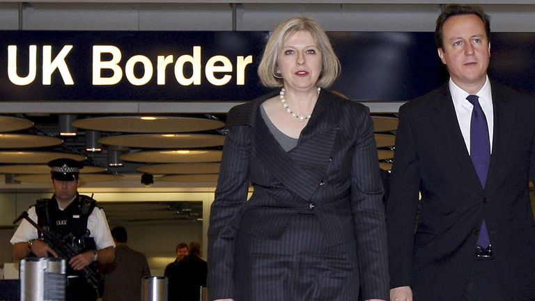 Britain's Prime Minister David Cameron and Home Secretary Theresa May (L) walk through Terminal 5 in 2010