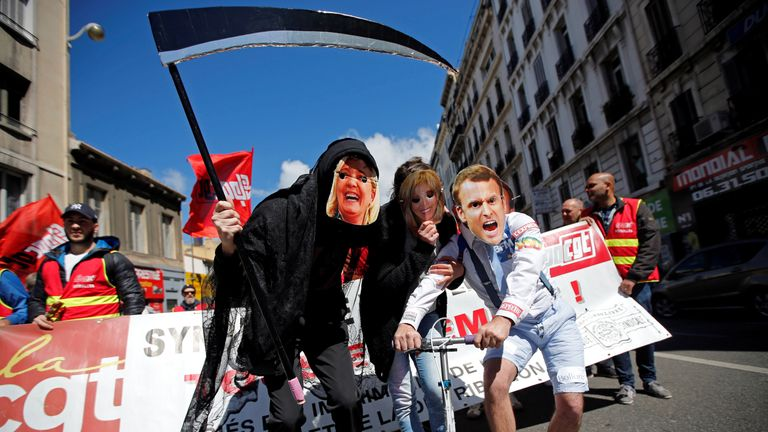Protesters wearing masks depicting Emmanuel Macron and Marine Le Pen in Paris