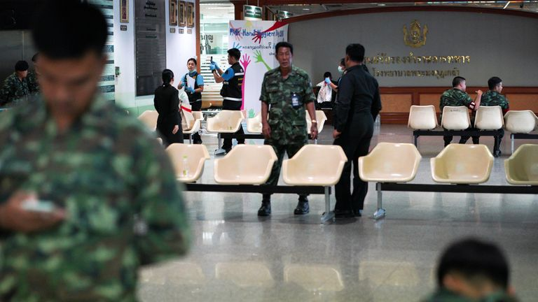 Thai military personnel and forensic officers stand near the site of the bomb blast