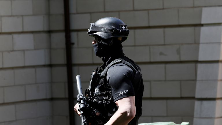 An armed police officer stands outside a residential property near to where a man was arrested in the Chorlton area of Manchester, Britain May 23, 2017