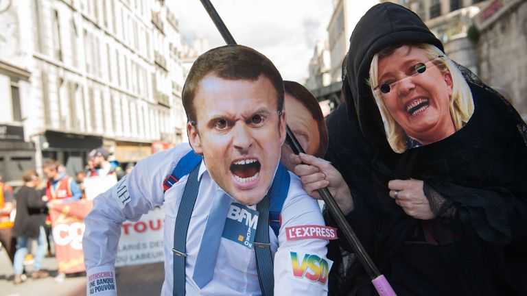 Protesters wearing masks of French presidential candidates Emmanuel Macron (L) and Marine Le Pen depicted as the Grim Reaper lead a march marking the annual May Day workers' rally in Marseille, southern France, on May 1, 2017