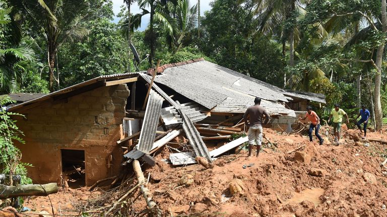 Residents walk past the remains of a structure hit by a mudslide in Kiribathgala