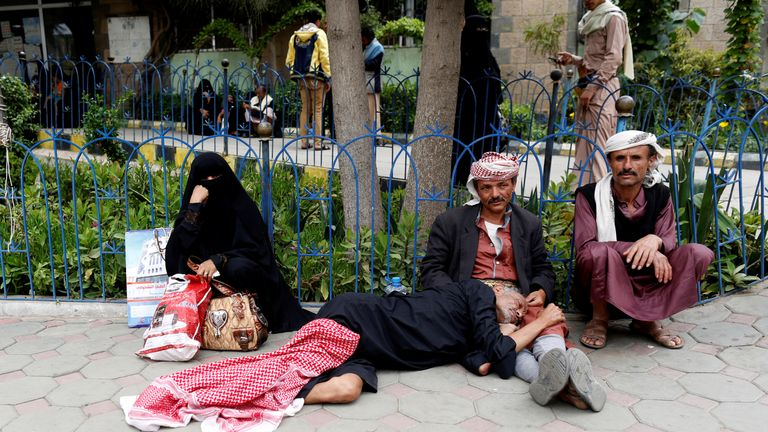 Relatives sit with a sick man waiting to be admitted to a hospital in Sanaa