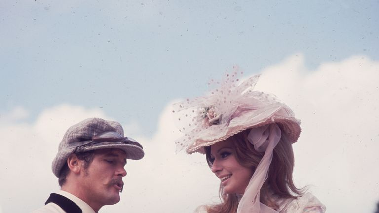 1968: Sir Roger Moore filming in the grounds of Woburn Abbey with his Italian co-star, Claudie Lange, for the film 'Crossplot'