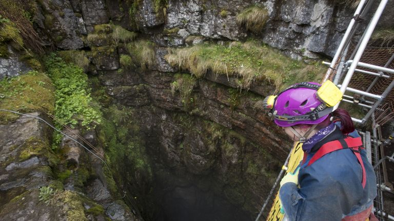 A potholer looks at the entrance to Gaping Gill