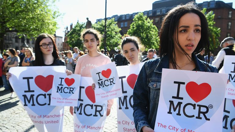 A group of girls carrying 'I love Manchester' placards is among the first to arrive at the vigil