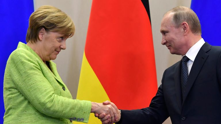 Vladimir Putin and Angela Merkel shake hands during their talks in Sochi