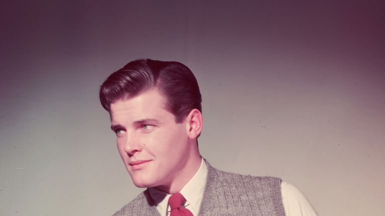1955: Roger Moore wearing a grey tank in his modelling days before James Bond