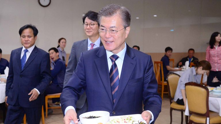 South Korean President Moon Jae-in carries a food tray in a Seoul staff canteen