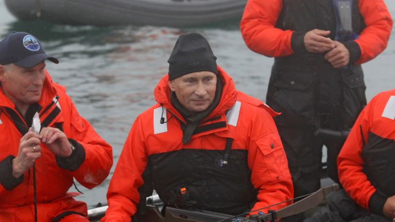 Vladimir Putin holding a crossbow as he hunts for whales in the Sea of Japan, August 2010