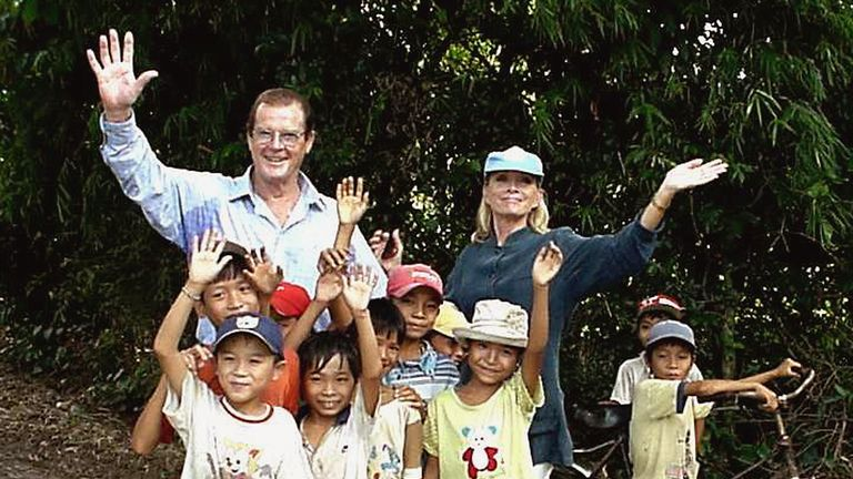 2003: Sir Roger Moore and his wife Kristina wave as they pose with children as part of a visit in his role as Goodwill Ambassador for the United Nations Children's Fund