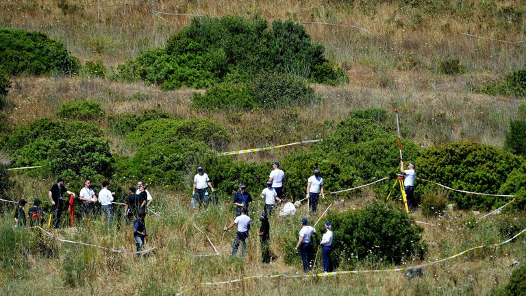 British and Portuguese officers search a patch of scrubland outside Praia da Luz in June 2014