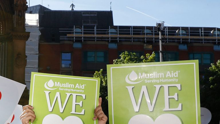 "Two people whose placards say ""Muslim Aid"" attend the vigil to show their support"