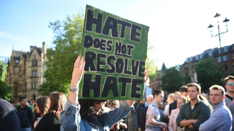 A woman holds up a sign that reads 'Hate Does Not Resolve Hate'