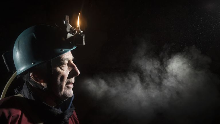 Condensation from a potholers' breath is seen as he uses a naked flame gas head torch whilst exploring Gaping Gill