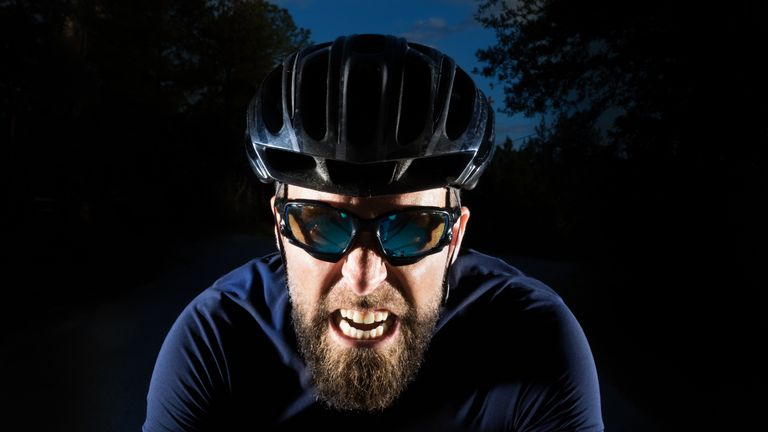 A cyclist grimaces as he pedals furiously