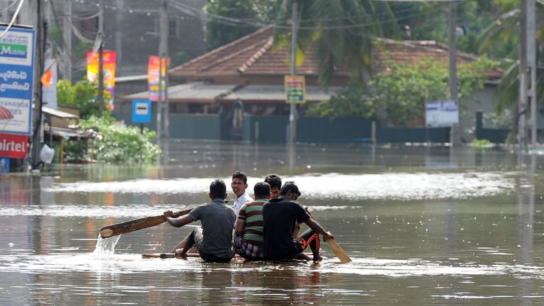 Sri Lankan residents make their way on a makeshift boat floodwaters in Nagoda in Kalutara district on May 29, 2017.