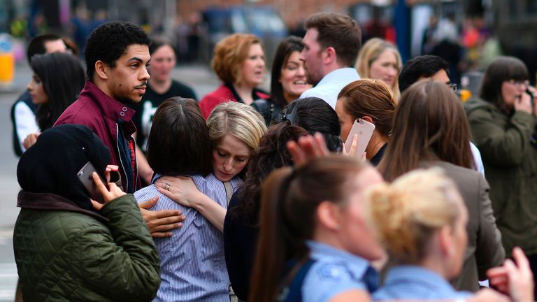 Shop staff console each other outside the Arndale