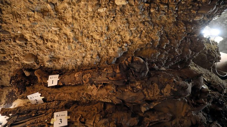 A number of mummies are seen inside the newly discovered burial site in Minya, Egypt