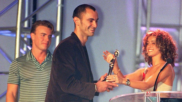 Robert Miles is presented with a Brit Award for Best International Newcomer by Louise Rednapp, as Gary Barlow looks on
