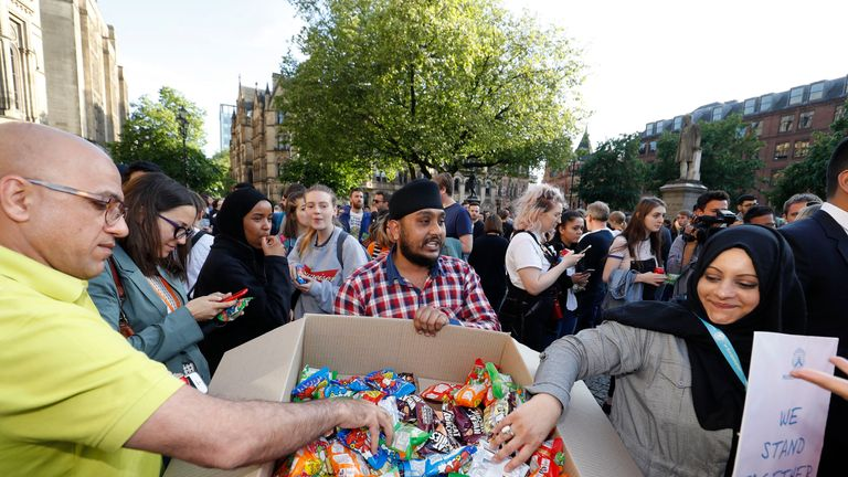 A man gives out food in Manchester's Albert Square to those attending the vigil
