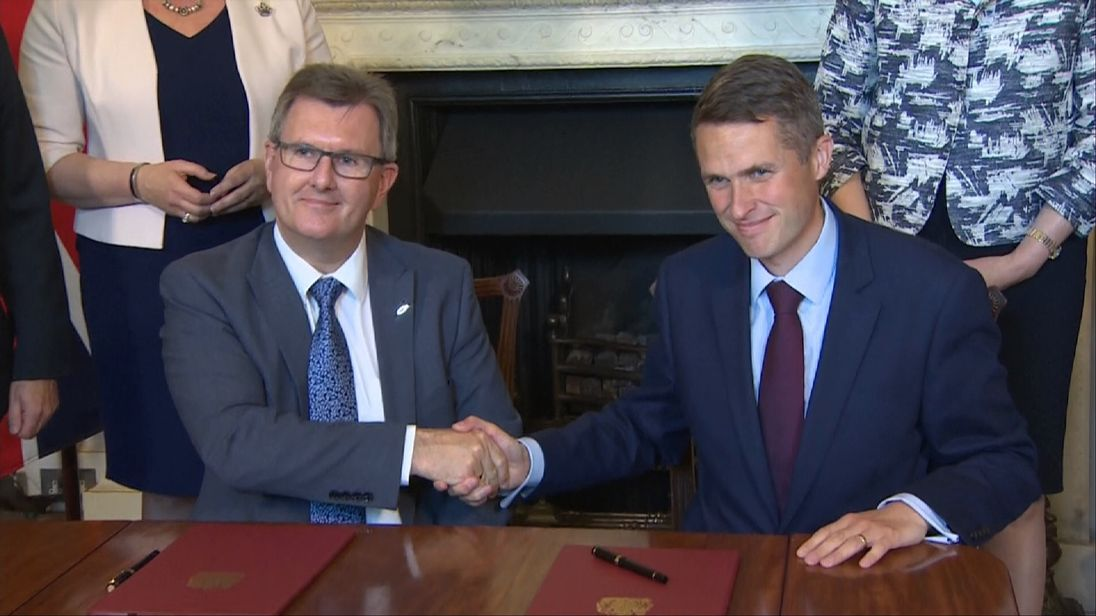 Sir Jeffrey Donaldson (L) and Gavin Williamson (R) shaking hands after signing the document