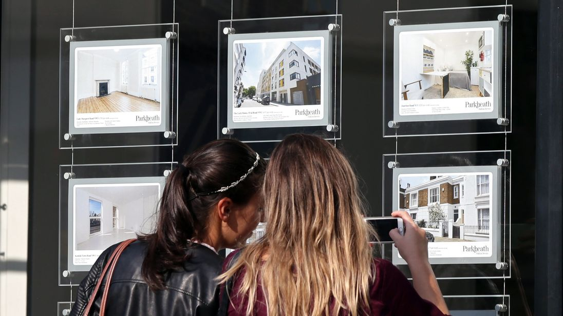 Two women looking in an estate agents window at the houses on offer