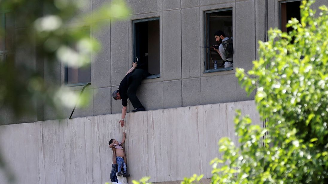A boy is evacuated during the attack on the Iranian parliament