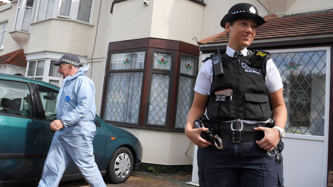 An officer stands outside a property as a forensics investigator walks behind her at a house that was raided by police, in Ilford, Britain, June 6, 2017