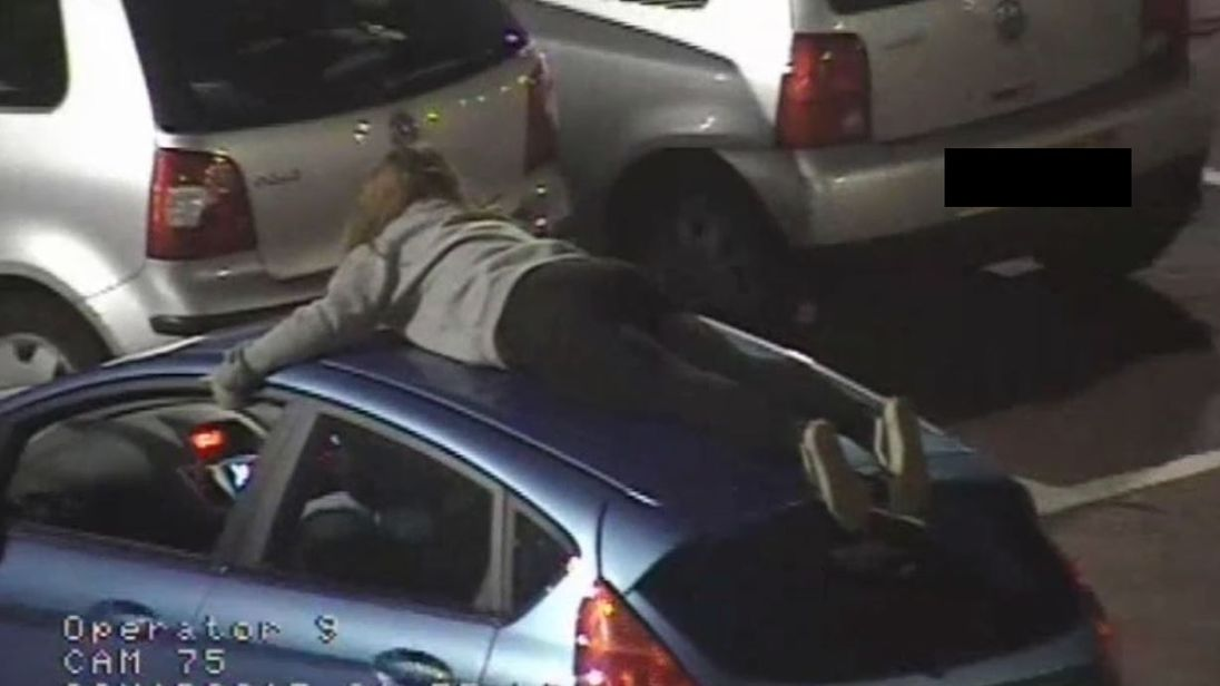 The girl was filmed lying flat on the roof of Ryan McMillan's car