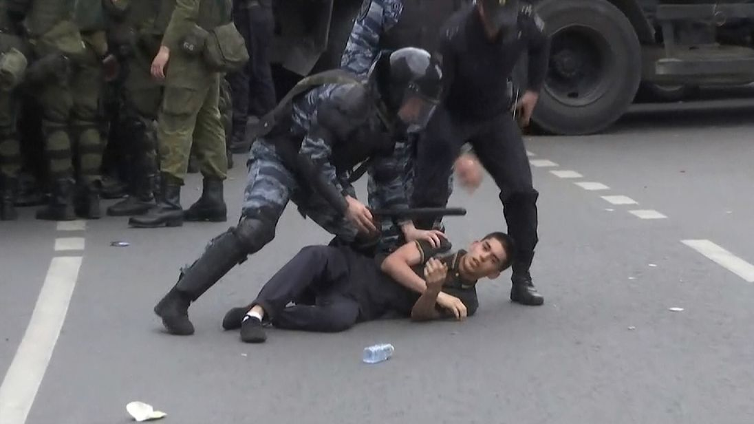 A protester is dragged to the ground in Moscow