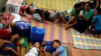 Evacuated residents lie on the floor at an evacuation centre outside Marawi