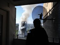 A man watches as smoke continues to rise from the building after a huge fire engulfed the 24 story Grenfell Tower in Latimer Road, West London
