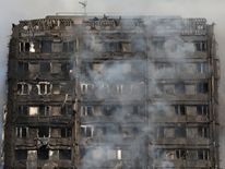 Smoke billows from a tower block severely damaged by a serious fire, in north Kensington, West London