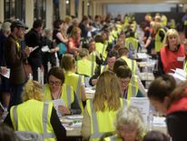 Counting staff verify postal votes at the Meadowbank Sports Centre counting centre in Edinburgh