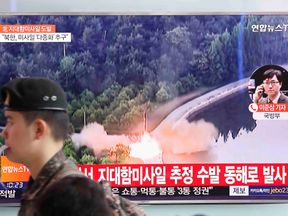 A South Korean soldier walks past a TV broadcast of a news report on North Korea firing what appeared to be several land-to-ship missiles off its east coast, at a railway station in Seoul, South Korea, June 8, 2017