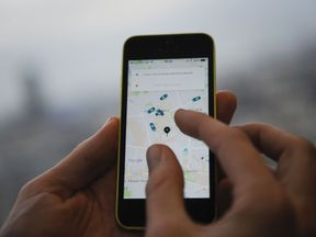 A man poses holding a smartphone showing the app for ride-sharing cab service Uber in London